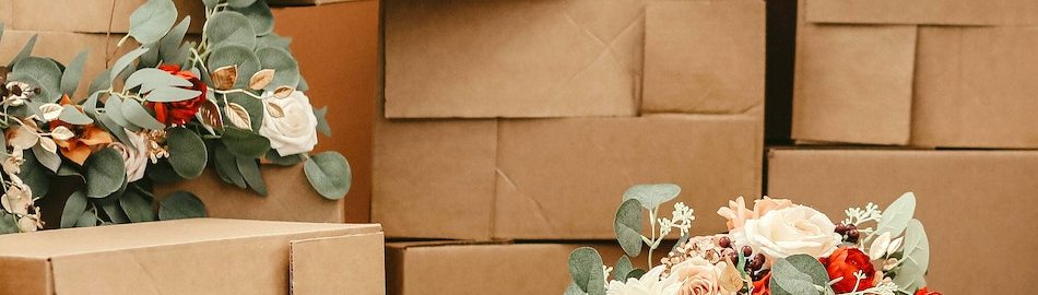 A stack of cardboard boxes against an orange wall. Atop some of the boxes are garlands of white and red flowers.